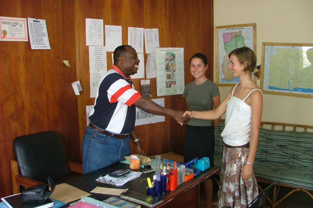 Young female volunteers shaking hands with Tom Davis in the office